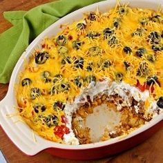 Mexican Casserole  1 1/2 cups crushed tortilla chips 1/2 lb ground beef 1 1/2 cups salsa 1 can chili with beans 8 oz sour cream 3/4 cup canned diced tomatoes, drained black olives 1/2 cup shredded cheddar cheese