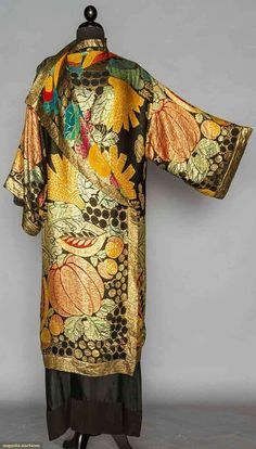 LAME & FRUIT EVENING COAT, 1920s. Black silk ground printed in multi colored fruit brocaded over in gold lame, kimono sleeves, F may be worn open or fastened at 1 shoulder.