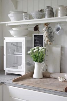 Nice kitchen ! great ways of organising...... shelves, hooks, cupboard and i love the flowers x