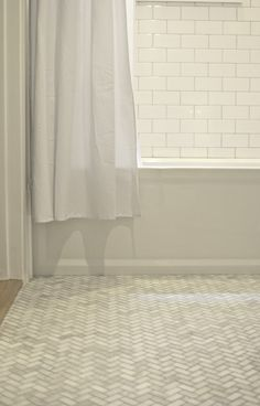 White subway tile walls and marble herringbone floors