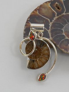 """Artisan handmade Ammonite Fossil pendant accented with 2 teardrop-shaped Fire Opal gemstones, bezel-set in 925-hallmarked sterling silver. Coordinating bracelet available separately. Length: 1.8"""" incl"""