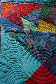 "Longarm quilting by The Running Chicken Quilting Co. (UK).  Kaffe Fassett quilt. ""The customer wanted the [flying] geese to stand out from the backgrounds so I decided that pebbles would be good.  I freehanded them and placed some sun blocks in the larger areas with my Statler."""