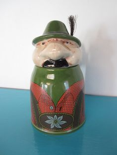 The best beer stein ever! It is a stein of a German man with a mustache, alpine hat with feather, wearing lederhosen. It is a heavy ceramic with a pewter hinge at the head. The head opens from the body.