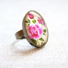 Bohemian Rose Garden Bronze Adjustable Cameo Ring Handmade rose garden cameo ring by Posh Adornments. ring features a brass cameo with a hot pink floral rose pattern.  band is adjustable, and can fit sizes 6-9. Anthropologie Jewelry Rings