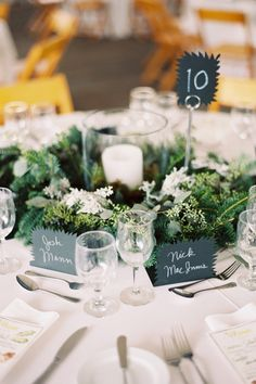 lovely tablescape with unique place cards, table card and leaf and branch wreath surrounding hurricane centerpiece | photo: Tec Petaja