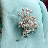The Queen`s new brooch made by Bronte Porcelain. The brooch resembles a bunch of flowers, that look like snowdrops or a similar flower.