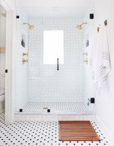 Equal parts classic and stylish, a white shower is designed to dazzle. Here, our favorite white shower tile ideas to try. Black White Bathrooms, White Bathroom Tiles, Wooden Bathroom, Small Bathroom, Bathroom Accents, Shower Tiles, Glass Shower, Black And White Bathroom Ideas, Master Bath Tile
