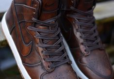 """The classic Nike Dunk High continues its new premium offerings with this edition in """"Burnished Leather"""". The classy makeover for the Dunk features a premium leather upper in brown given a burnished treatment for a stylish aged effect. Add in flat waxed laced, and a gum rubber sole and you have yourself one fancy edition …"""