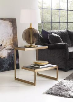 Show off your flair for modern design with this one of a kind end table. This wood and brass table features two staggered-height shelves that makes this a unique accent to any contemporary living space.
