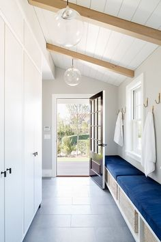 Entryway with matching bulb pendant lights, exposed wooden beams, and a blue bench lining the wall