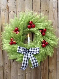 This adorable traditional looking Christmas wreath with candle would look beautiful on your front door to welcome your guest this holiday season. Its made with deco mesh, little red plastic bulbs for the berries, plastic candle and a black and white buffalo check ribbon. All my wreaths are handmade