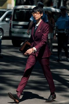 janie cai, fashion director for esquire singapore is in the middle of a walking stride. she is wearing a burgundy pant suit, leather shoes with buckles, a sweater underneath and a button up shirt.