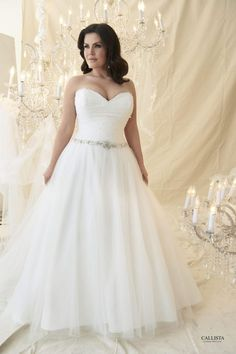 Romantically styled full ball gown in billowing tulle. Corset bodice delicately pleated and scattered with pearls and crystals. Waistline enhanced with a crystal beaded belt.