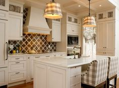 I love this kitchen! Tan, brown, creamy white! The backsplash is great, & love the fabrics used on the chairs at the kitchen island.
