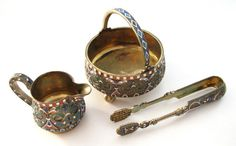 THE SET CONTAINS A MILK CUP, A SUGAR HOLDER AND A SUGAR TONGS. AS YOU CAN SEE THE SET HAS A NICE RUSSIAN DESIGN - COMBINATION OF SILVER AND PRETTY ENAMELED ORNAMENTS. ALL THREE PARTS OF THE SET ARE MARKED BY A.S 88 SILVER AND DATE 1894, MASTER MARK - A.L. ( ALL INITIALS ARE WRITTEN IN CYRILLIC RUSSIAN ).