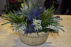 Table centerpiece made in stone bowl,with eryngium questar,craspedia,leucadendron,white wax flower,white veronica flower,eucomis and grevillea spider leaves,designed by Adrian Ionita