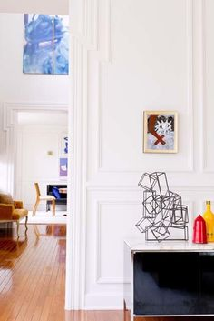 Perfectly aligned 14 inch deep doorways framed in custom millwork offer beautiful views from room to room. In the living room foreground, the small painting is by Antoni Tapies and red bullet is by artist James Salaiz. A glimpse of the dining room is seen beyond.