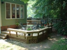 A custom ground-level deck featuring wrap-around benches and diagonal decking built by Raleigh Deck Contractor Anthony and Company Construction - Raleigh Area Deck