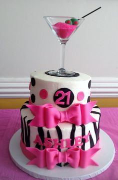 Two tier women's 21st birthday cake with zebra stripes pink bows and martini glass on top.JPG