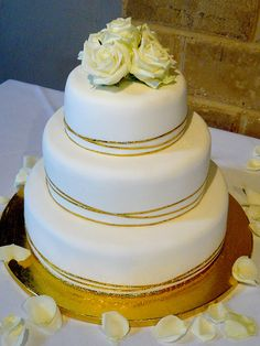 Wedding Cake White frosting with gold ribbon and dragges