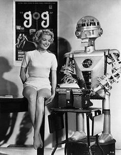 1953 – GARCO – Created by Harvey G. Chapman Jr. (American) - Garco with starlet Sally Mansfield (who was a regular on the TV show Rocky Jones, Space Ranger) promoting the 1954 film, Gog. Garco is at a typewriter supposedly typing out a press release on a classic manual typewriter.