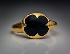 This powerful Byzantine medieval gold ring is featuring an ancient symbol of good luck - the quatrefoil.    Circa 10th - 11th century.    The ring is set with a cabochon black onyx in an openwork quatrefoil-shaped bezel.