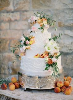 Decadent buttercream wedding cake with flowers and peach