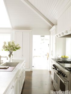 The wide-plank heart pine floor, stained a dark chocolate brown, conveys a feeling of age and keeps an all-white kitchen from floating