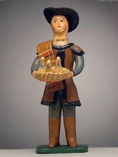 Pastor ofertante em pé, com cesto com 3 pombas (17,8 x 6,5 cm). Autor desconhecido (séc. XX). Museu Nacional de Etnologia, Lisboa.