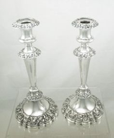"Pair of Large and Heavy Silver Plated Candlesticks. They have ""V"" shaped bodies with embossed grape, leaf and scroll patterns around the removal sconces, the two circular parts of the main body and the on the large filled circular bases. These large circular bases also have wavy rims and are both covered with a green baize.    £112"