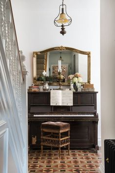 Original coloured tiles give the large hall plenty of period character. Carla bought the piano as a gift for Ben some years ago. 'It doesn't get played much now, but it's still a beautiful object,' she says. The mirror above is one of a pair inherited from Ben's parents   #victorian #victorianinterior #victoriantiles #victorianhomeinspiration #victorianhallway