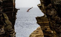 Artem Silchenko of Russia diving 29m from the rock monolith during the first round of the third stop of the Red Bull Cliff Diving World Series in Islet Vila Franca do Campo, Azores, Portugal, Friday July 20, 2012. (AP Photo/Red Bull, Dean Treml)