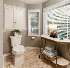 • Full overlay custom al-der custom wood cabi-netry with diamond white paint and brown glaze transforms the bathroom. Fireplace Remodel, Custom Wood, White Paints, Overlay, Glaze, Toilet, Bathroom, Diamond, Brown