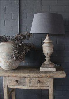 Mooie oude, houten, landelijke sidetable met prachtige lamp en kruik met dadeltak. Prachtig hoekje in een landelijk interieur.