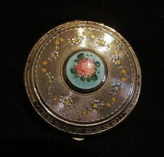 This is a wonderful vintage 1930's Art Deco style silver tone powder compact. The piece is in wonderful condition with a pretty enameled guilloche center medallion with a hand painted pink rose and gr