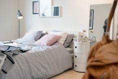 Uma cama convidativa, mesinha de cabeceira pequenininha essencial pra deixar o celular carregando e fazer uma graça com um abajourzinho pequeno