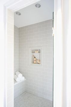 A glass door opens to a walk-in shower clad in light gray subway wall tiles fixed surrounding a tile framed niche covered in mini white hex tiles. 28 Inspirational Walk in Shower Tile Ideas for a Joyful Showering Gray Shower Tile, White Subway Tile Bathroom, Tile Walk In Shower, Subway Tile Showers, Grey Subway Tiles, Glass Tile Bathroom, Bath Shower, White Shower, Bathroom Tile Showers