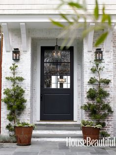 could I DIY this? whitewash the brick at front of the house - love this image. Entrance to a white washed brick house with rusty metal planters on either side, whitewashed stone stairs, a black front door, and lantern style lights Interior Exterior, Exterior Colors, Exterior Paint, Exterior Design, Stone Exterior, Exterior Homes, Brick Design, Interior Doors, Black Front Doors