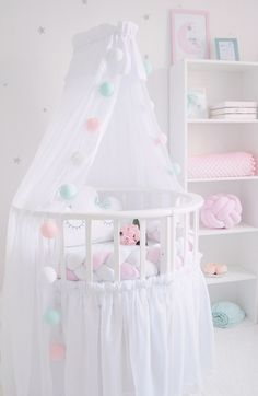 Adorable crib canopy with matching crib skirt. Love the pink and blue pom pom garland as an accent with the canopy. Add a braided crib bumper for extra security and style. The colors are so soft and are perfect for a little girl!
