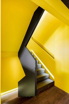 Naturehumaine used strips of black to articulate circulation throughout the house. A focal point of the interior is a black and yellow stairwell with geometric cut-outs.