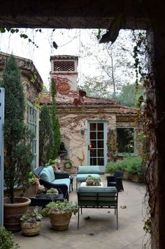 Penelope Bianchi's lovely patio- want to plant vines and ivy on our house like this- I bought the milk paint in a color more close to the doors shown here