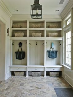 Stylish Mud Room with white built-ins with storage and a beadboard backing. Amazing tile flooring and lantern light fixture.