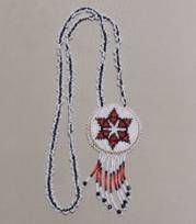 """Rosette Necklace The Rosette Necklace is approximately 2"""" in diameter, leather back with beadwork around the edge, bead dangles and a bead chain for wearing. Made by E. Descheney (Navajo)"""