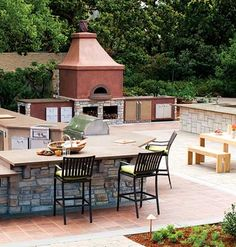 Anyone can pick up a little charcoal grill and call it a party. However, this open-air kitchen goes way beyond the grill to include a wine bar, two grills, a pizza oven, and tons of workspace
