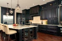 Kitchen - dark cabinets and wood floors. Upper cabinets with glass doors. Pendant lights - LOVE