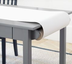 Instead of a whiteboard table, mount a roll of butcher paper on one end, paper cutter on the other, paperweights scattered around.