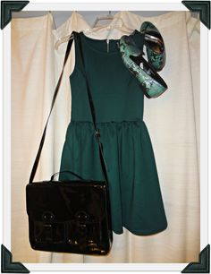 green dress, snakeskin print loafers, and bag