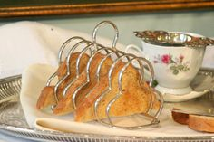 Great silver plate toast rack!  The 7 bars are bent into a trefoil shape with a loop handle, sitting on four ball style feet; holds 6 slices of bread/toast.  Perfect addition to a breakfast tray or table.