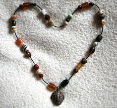 Kette aus meist naturfarbenen Glasperlen mit afrikanischen Muster und afrikanischen Kopf.  Diese Kette ist etwas Besonderes, da ich den afrikanis...