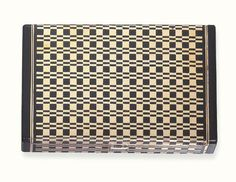 AN ENAMEL AND GOLD VANITY CASE, BY CARTIER   The rectangular case decorated with a black enamel geometric motif with black enamel terminals, to the baguette-cut diamond push-piece, opening to reveal a fitted mirror, lipstick holder and powder compartment, circa 1935, 8.5 x 5.5 x 1.5 cm., with French assay marks for gold  Signed Cartier, no. 0901